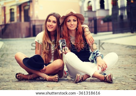 Outdoor lifestyle portrait of two best friends, having fun together, joy and happiness, wearing trendy wool hat, stylish vintage bohemian outfits. Fall fashion. Photo toned style instagram filters.