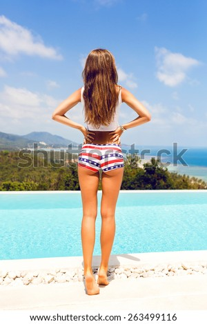 Outdoor lifestyle portrait of woman with perfect body and long legs in sexy shorts put  and enjoy her freedom in amazing tropical island . Perfect view on ocean and mountains. - stock photo