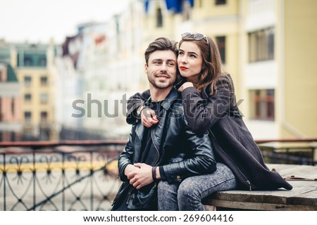 Outdoor lifestyle portrait of young couple in love  in old town on the street, couple sitting, city, europe - stock photo