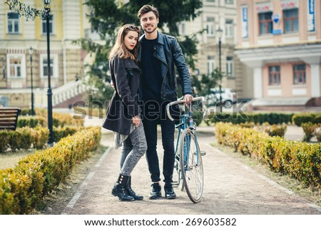 Outdoor lifestyle portrait of young couple in love standing in old town on the street, bike, hipsters, lifestyle, youth - stock photo