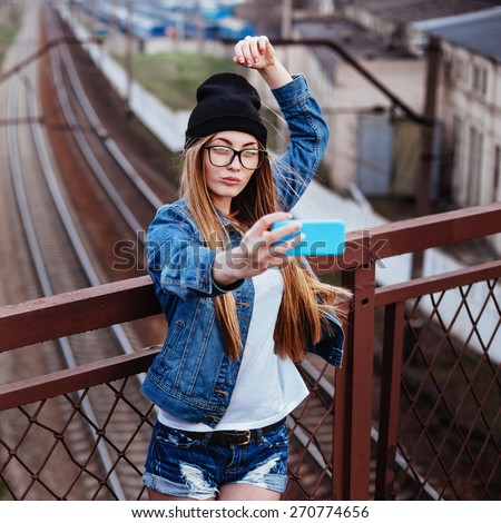 Outdoor lifestyle portrait of young sexy blonde hipster woman posing for selfie and laughing. Wearing jeans jacket, hipster black hat and glasses.  - stock photo