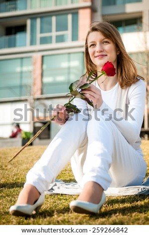 Outdoor lifestyle portrait of young woman daydreaming  with red rose - stock photo