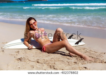 Outdoor lifestyle stylish portrait of young sexy tanned blonde woman in bikini posing in summer on the beach - stock photo