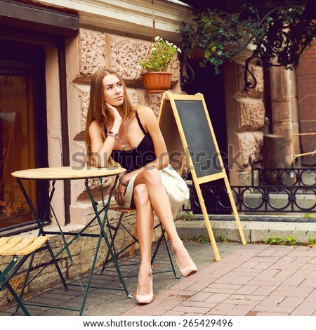 Outdoor lifestyle summer fashion hipster style portrait of pretty young dreaming waiting in street cafe woman sitting on the table