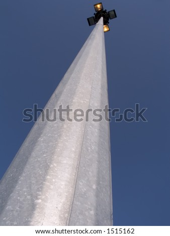 Outdoor lights in perspective over an huge high pylon - stock photo