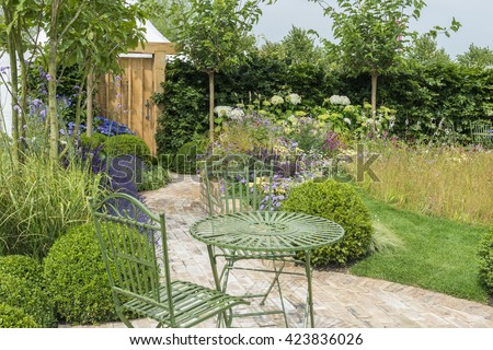 Outdoor living - gazebo, chairs and table set up in the garden - stock photo