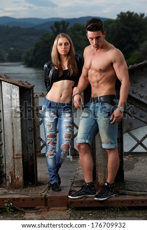Outdoor natural portrait of a gorgeous couple fitness models.Gymnastics girl.Fashion colors.  - stock photo