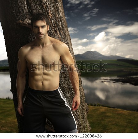 Outdoor natural portrait of a gorgeous male fitness model - stock photo