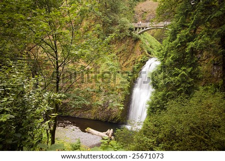 Outdoor nature park with waterfall and bridge - stock photo