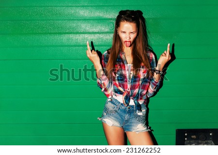 Outdoor night fashion portrait of young sexy pretty brunette spoiled crazy girl showing tongue and middle finger gesture on green background  - stock photo