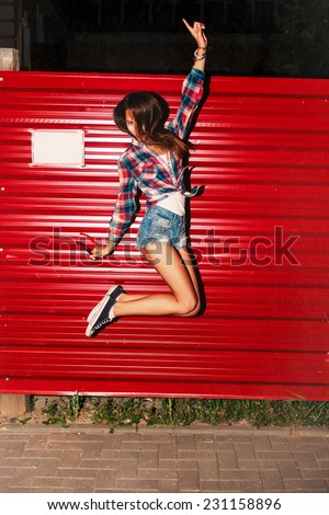 Outdoor night flash portrait of pretty sexy tanned young girl jumping going crazy and happy fun on the street on red wall background  - stock photo