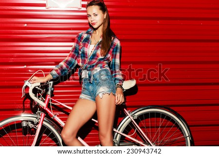 Outdoor night flash portrait of pretty sexy tanned young girl posing on red wall background with vintage pink retro bicycle and have fun  - stock photo