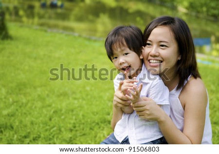 Outdoor park happy Asian mother and son - stock photo
