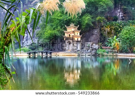Outdoor park landscape with stone bridge and lake. Gate entrance to old Bich Dong pagoda complex. Ninh Binh, Vietnam - travel destination.