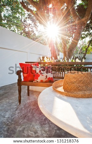Outdoor patio seating are with nice bench at sunset - stock photo