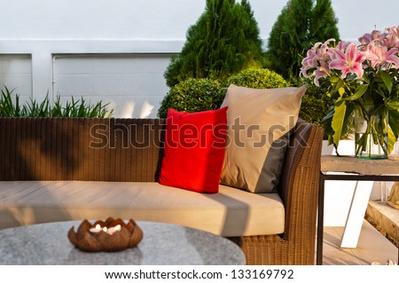 Outdoor patio seating area with nice Rattan sofa at sunset - stock photo