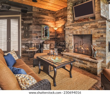 Outdoor Patio with Couch, Chairs, TV, Fireplace, and Roaring Fire - stock photo