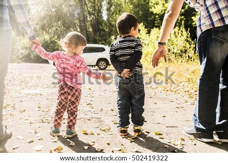 Outdoor photo in summer park. Casual dress. Sunset light rays. Parents - mother, father and kids - daughter, son holding hands each other against white SUV big car.