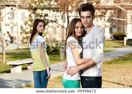 outdoor photo of a young woman jealous on a happy couple - stock photo