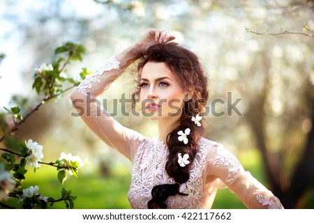 Outdoor photo of beautiful charming brunette woman in elegant lacy dress with flowers in her hair posing in spring blossom garden.Pretty young woman with blue eyes dreaming and looking afar.Fairy tail - stock photo