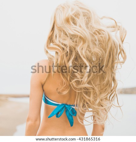 Outdoor photo of beautiful young happy woman at the sea - stock photo