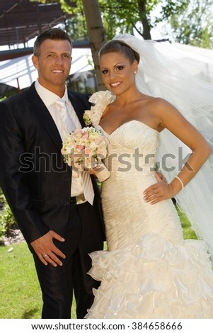 Outdoor photo of happy young couple on wedding-day, embracing, smiling.