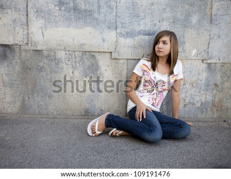 Outdoor photo of pretty teenage girl seated on pavement against grunge wall. - stock photo