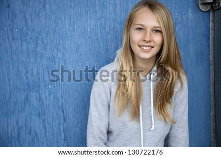 Outdoor photo of pretty, young teenage girl standing against blue wall.