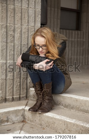 Outdoor photo of young teenage girl seated on ground, hugging knees, distraught facial expression.