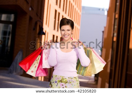 outdoor picture of happy woman with shopping bags - stock photo