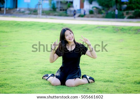 outdoor portrait  asian girl in black dress  with perfect smile at the park