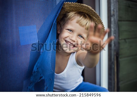 Outdoor portrait:  Cheerful kid with straw hat leaning out a window, smiling and waving  - stock photo
