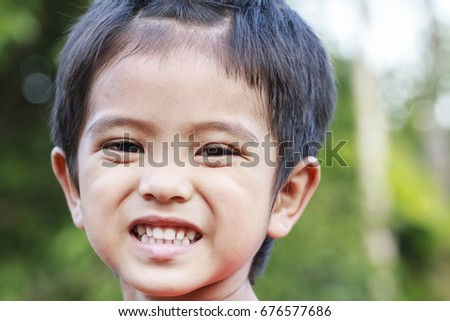 Outdoor portrait head shot of Asian little boy smiling face looking with eyes contact to camera