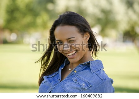 Outdoor portrait of a beautiful African American woman winking  - stock photo
