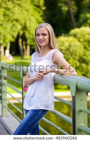 Outdoor portrait of a beautiful blonde smiling woman standing on the bridge in the park