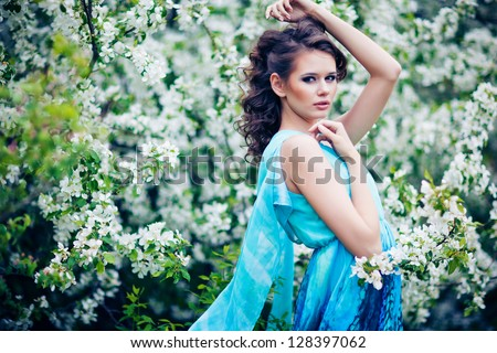 outdoor portrait of a beautiful brunette woman in blue dress among blossom apple trees - stock photo