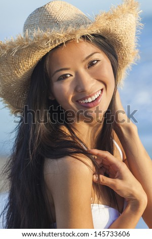 Outdoor portrait of a beautiful Chinese Asian young woman or girl wearing a white bikini and straw cowboy hat at a beach - stock photo
