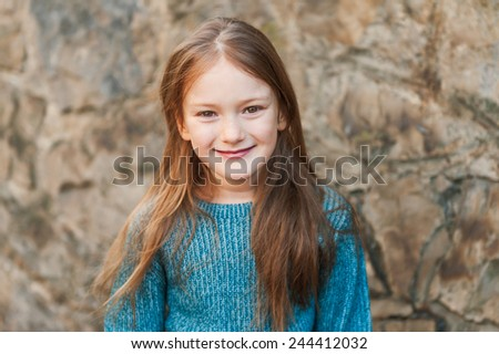 Outdoor portrait of a beautiful little girl of seven years, wearing blue pullover - stock photo