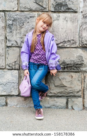 Outdoor portrait of a beautiful preschool girl wearing jeans, purple top and rain jacket, shiny tennis shoes, standing next to stone wall - stock photo