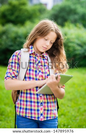 Outdoor portrait of a beautiful teenager girl in casual clothes with backpack holding digital tablet in her hand, typing and reading - stock photo