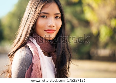 Outdoor portrait of a beautiful young Asian woman smiling. - stock photo