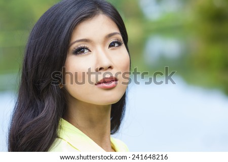 Outdoor portrait of a beautiful young Chinese Asian young woman or girl by a lake with reflections - stock photo