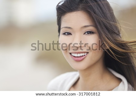 Outdoor portrait of a beautiful young Chinese Asian young woman or girl with perfect teeth - stock photo