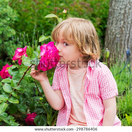 Outdoor portrait of a cute little blond boy, smelling beautiful bright pink rose in the garden - stock photo