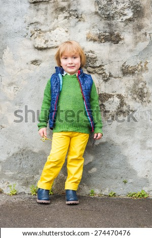 Outdoor portrait of a cute little blond boy wearing colorful clothes, yellow jeans, green pullover, blue waistcoat and boots, standing next to stone wall in a city - stock photo