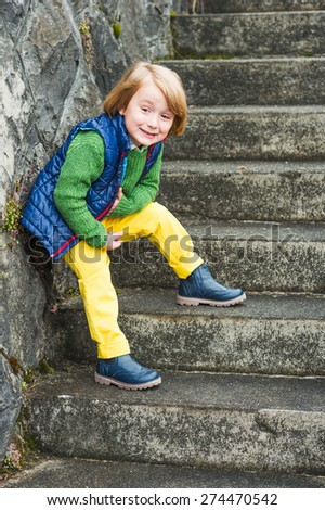 Outdoor portrait of a cute little blond boy wearing colorful clothes, yellow jeans, green pullover, blue waistcoat and boots, standing on stairs in a city - stock photo