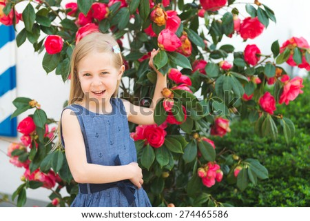 Outdoor portrait of a cute little blond girl, wearing blue dress, standing between bright pink flowers - stock photo