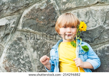 Outdoor portrait of a cute little boy holding sunflower - stock photo