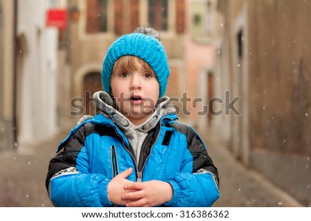 Outdoor portrait of a cute little boy in a city under snowfall, wearing warm blue jacket and knitted hat - stock photo