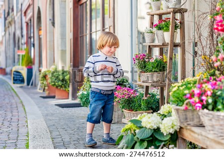 Outdoor portrait of a cute little boy, playing with flowers in front of a flower shop - stock photo